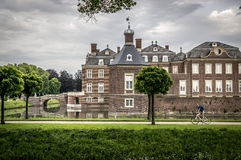 Cycling near a palace. Girl riding a bike near Nordkirchen palace in Muensterland, Germany Royalty Free Stock Image