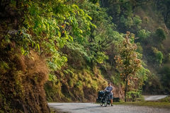 Cycling in Nepal. Woman pushing her bicycle uphill on a mountain road in Nepal Stock Image
