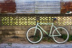 Bike and old fence cement with corrugated iron which as the background. Cycling and old fence cement with corrugated iron which as the background Royalty Free Stock Photography