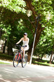Cycling in the park. Girl cycling in the park. She's wearing white sport clothes, cap, her bicycle is red. It's a sunny summer day Stock Photography
