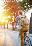 Cycling in the park. Young woman cycling around on vintage bicycle royalty free stock photos