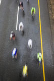 Cycling Riders Speed Blurs. Pele-ton cyclists racing pedaling and going fast  under the bridge at speed blur pace Royalty Free Stock Photography