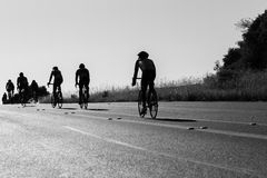 Cycling Road Silhouetted Black White. Cyclists Cycling up hill silhouetted road race Stock Photo