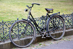 Cycling round the rails. Old black bicycle wheel on rail Stock Photo