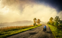 Cycling on the rural roads. Woman cycling alone on the narrow rural roads in Poland Stock Photography