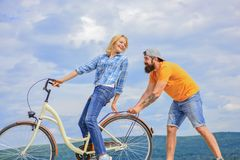 Cycling service. Mechanic helps maintain bicycle. Supportive service. Woman rides bicycle sky background. Man helps keep. Balance ride bike. Girl cycling while royalty free stock images