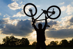 Cycling silhouette rider with bicycle holding up Royalty Free Stock Photography