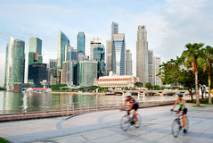 Cycling in Singapore. Two unidentified cyclists in Singapore. Singapore downtown on the background Stock Photos