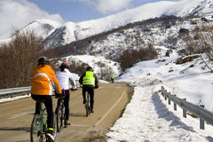Cycling in the snow. Some friends doing sport with his mountain bikes in the snow of Cantabria, Spain Royalty Free Stock Photos