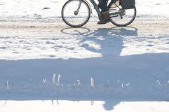 Cycling in snow. A person cycling on a snowy road Royalty Free Stock Photo