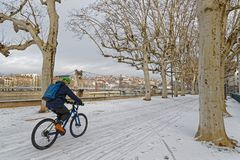 Cycling on snow through the trees. LYON, FRANCE, March 1, 2018 : Pedestrian walkways on Rhone river banks, as a cold spell rages in all Europe and the Capital of Stock Image