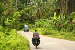 Cycling through Sumatra. Female cyclist cycling on Trans-sumatran Highway in Sumatra, Indonesia Royalty Free Stock Image