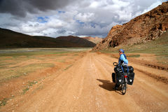 Cycling through Tibet. Single female cyclist on the bicycle on the remote road in Eastern Tibet Royalty Free Stock Image