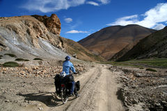 Cycling through Tibet. Single female cyclist on the bicycle on the remote road in Eastern Tibet Royalty Free Stock Photo