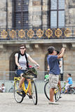 Cycling tourist on Amsterdam Dam Square Stock Photo