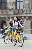 Cycling tourists on Amsterdam Dam Square Stock Photos