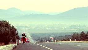 Cycling traveler on the highway moving up. Female cycling traveler moving up along the highway stock video
