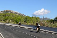 Cycling triathlon exercise healthy. Triathletes cycle up a scenic hill in Majorca during the Challenge Mallorca half Ironman distance triathlon Royalty Free Stock Images