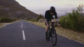 Cycling up a hill. Wide angle shot of a male cyclist climbing up a mountain road. Man cycling on steep road on a hill stock video footage