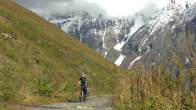 Cycling up the mountain road stock video footage