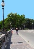 Cycling and walking in bridge. A man walking and a woman cycling at Verdi Bridge (Ponte Verdi), Parma, Italy Royalty Free Stock Images