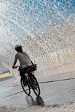 Cycling through water. Female cyclist passing under a urban waterfall Stock Photos