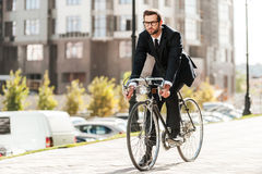 Cycling is the way to progress!. Full length of handsome young businessman looking forward while riding on his bicycle Royalty Free Stock Photos