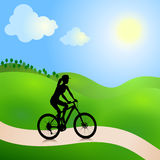 Cycling woman. Girl cycling on the road in the summer day Royalty Free Stock Photography