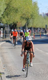 Cycling woman wearing black tank-top followed by competitors Stock Image