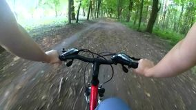 Cycling in the woods on a dirt road stock video