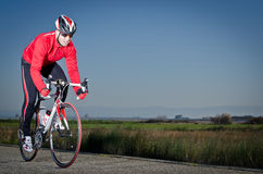 Cyclist. Man on road bike riding down open country road Royalty Free Stock Images
