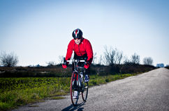 Cyclist. Man on road bike riding down open country road Royalty Free Stock Photo