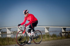 Cyclist. Man on road bike riding down open country road, bridge on background Royalty Free Stock Photography