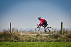 Cyclist. Man on road bike riding down open country road Stock Photography