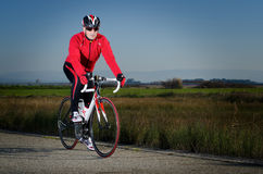 Cyclist. Man on road bike on open country road background Royalty Free Stock Photography