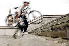 Cyclist. Blurred cyclist carrying his bike in london royalty free stock photo
