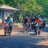 A cyclist accompanied by a group of motorcyclists. Sri Lanka. ANURANHAPURA, SRI LANKA - CIRCA APR 2013: A cyclist accompanied by a group of motorcyclists Royalty Free Stock Photography