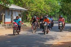 A cyclist accompanied by a group of motorcyclists. Sri Lanka. ANURANHAPURA, SRI LANKA - CIRCA APR 2013: A cyclist accompanied by a group of motorcyclists Stock Images