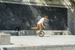 Cyclist acrobat. Young man doing tricks on his  bicycle Royalty Free Stock Photos