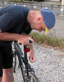Cyclist adjusting the saddle. Detail of a bicyclist adjusting the saddle level Royalty Free Stock Photos