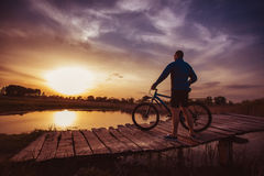 The cyclist admires the wonderful sunset on the bridge Stock Photography