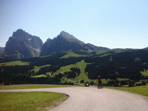 Cyclist, Alpe di Siusi, Italy. Cyclist along winding road through Alpe di Siusi in Italy Stock Images