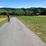 Cyclist in Alpe di Siusi. Man on bicycle riding road through Alpe di Siusi in Italy on summer day Stock Images