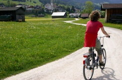 Cyclist in Alpine Meadow. Cyclist on path in Austrian Alps Royalty Free Stock Images