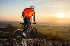 A cyclist with a backpack on a background of blue sky and the field. Royalty Free Stock Images