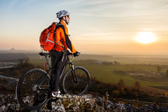 A cyclist with a backpack on a background of blue sky and the field. Royalty Free Stock Photography