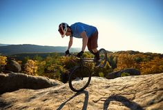 Cyclist balancing on front wheel on trial bicycle on boulder. Professional cyclist riding on front wheel on trial bike. young Sportsman rider balancing on the royalty free stock photos