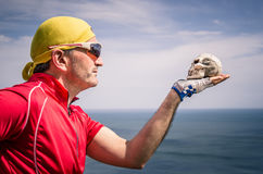 Cyclist with bandana Headband looking at a Skull. Dramatic portrait of a cyclist with bandana headband looking at a skull Stock Photography