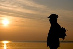 Cyclist on a beach. An adult cyclist, man wearing a protective helmet, gloves, sunglasses and backpack, at the beach, looking at the setting sun. The Baltic Sea stock photos