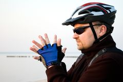 Cyclist on a beach. An adult cyclist, man wearing a protective helmet, gloves and sunglasses, at the beach, looking on Stock Image